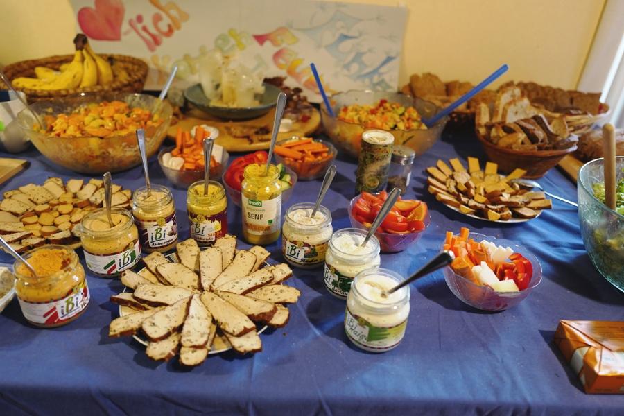 Buffet mit Tofu, Aufstrichen, Obst, Brot und Salat