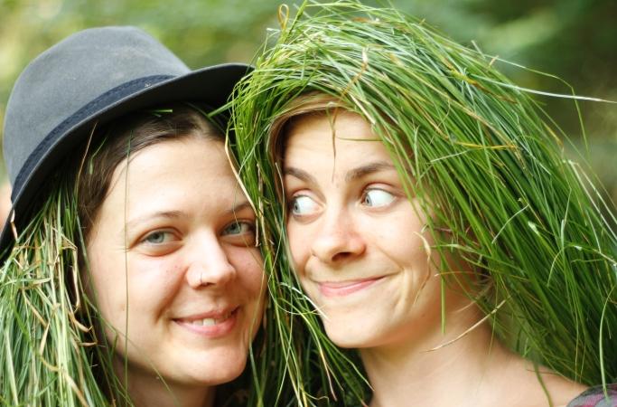 Zwei kreative junge Frauen tragen Gras als Haare und lächeln. Die linke trägt einen Hut.