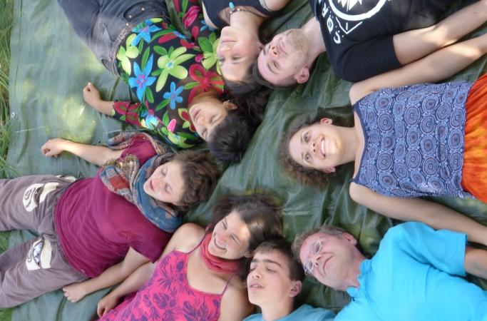 Acht Menschen liegen Schulter an Schulter im Kreis und träumen fröhlich oder entspannt vor sich hin