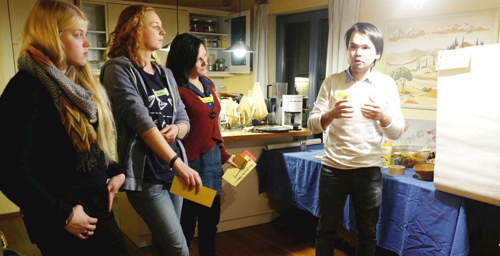 Drei junge Frauen hören einem jungen Mann bei einem Vortrag zu