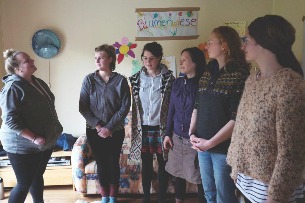 """Sechs junge Frauen stehen vor einem kreativen Plakat mit der Aufschrift """"Blumenwiese"""""""
